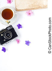 the vintage film camera, old book, flower and tea on white background .