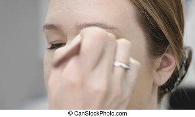 The visage master making make-up for young model -...