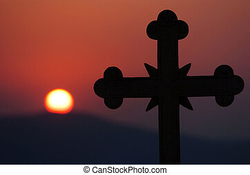 The vision of a cross is seen against the backdrop of the sun setting in Greece.