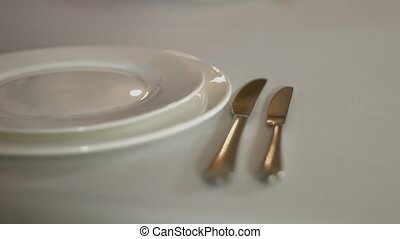 The waiter laid out cutlery on a table with white tablecloth...