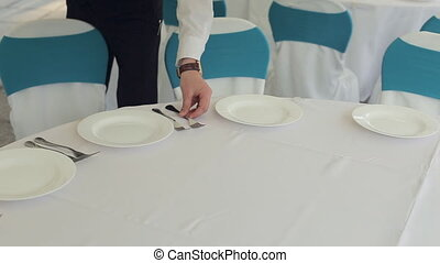 The waiter lays forks on a banquet - The waiter lays forks...