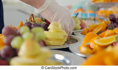 The waiter lays out on a platter variety of fresh and juicy fruits