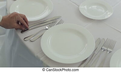 The waiter neatly laid out cutlery on a table with a white...