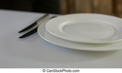 The waiter neatly laid out cutlery on a table with white...