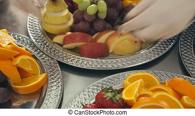 The waiter nicely lays out sliced apples on a plate with fresh fruit for banquet