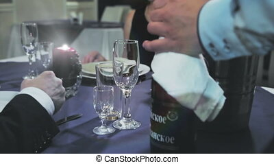 the waiter opens standing on the table A couple of champagne rips off his foil