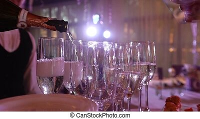 The waiter pours champagne in wineglass, in a restaurant, The waiter pours champagne in crystal glasses, Restaurant interior, buffet table, Waiter in white gloves, close-up