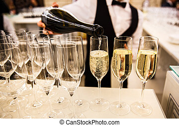 The waiter pours champagne into a glass. Empty glasses on the table. A row of empty champagne glasses.