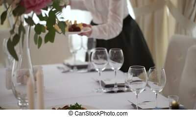 The waiter puts a plate of snacks on the wedding table close up