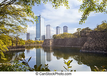 Wall and moat around Osaka Castle and skyscrapers of Osaka Business Park on background