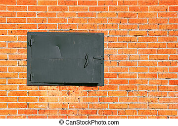The wall of red brick with a metal hatch