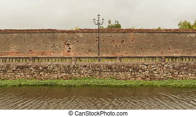 The wall of the fortress with a small river