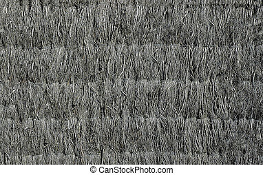 The wall of the old house is fortified with dry grass of gray color .Texture or background.