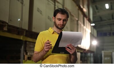 The warehouse worker makes an inventory of the goods. The male storekeeper recounts the goods in the warehouse and makes notes. Manager work in the warehouser