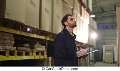 The warehouse worker makes an inventory of the goods. The male storekeeper recounts the goods in the warehouse and makes notes, warehouse worker, industrial interior, a warehouse interior