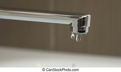The water faucet. Drops of water seep through the water faucet. Close-up