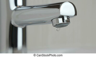 Drops of water seep through the water faucet - The water...