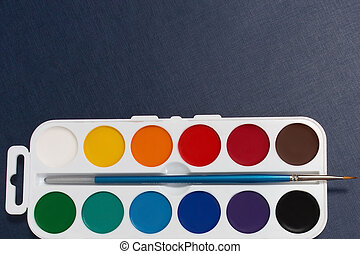 watercolor paints on a blue background