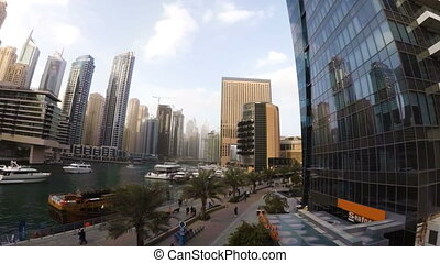 The waterfront Dubai Marina with a promenade where walking tourists and marine canal where sailing boats
