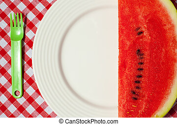 the watermelon on picnic tablecloth