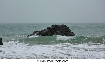 The waves beat against the rock