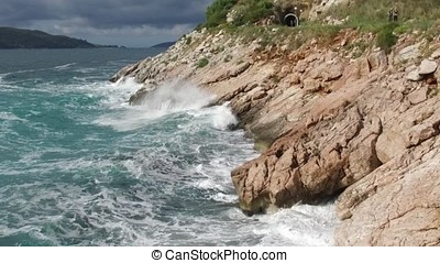 The waves breaking on a stony beach, forming a spray. Footage. Splashing waves on the rocks of the sea