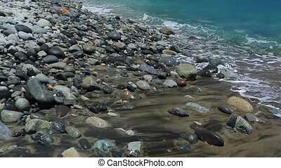 The waves creep up to the gray stones and lick them. Calming...
