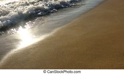 The waves on the beach at sunset