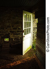 An open door leading from an empty chicken coop from which the chickens have flown.