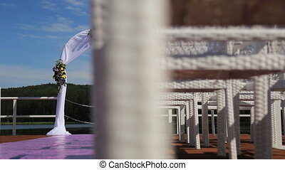 The wedding arch with flowers is seen through the cane chairs made of wood. It's located on the cost of the lake with beautiful landscape.