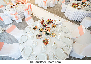 The wedding Banquet hall is decorated with flowers and bows