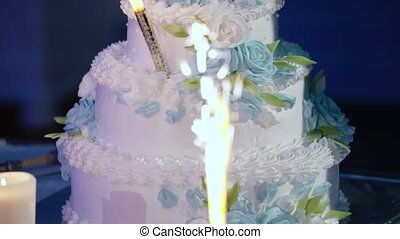 The wedding cake with fireworks stand on the table in restaurant