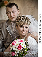 The wedding pair sits in a room