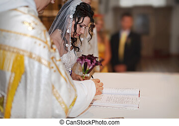 The wedding signature. Bride signing the register