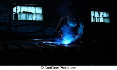 The welder works in a mask in slow motion. Sparks fly in...