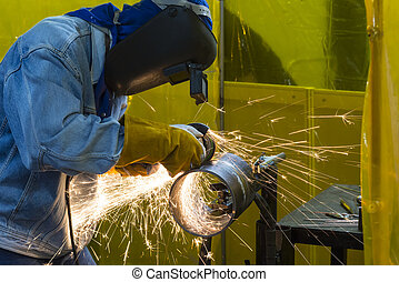 The welding craftsman grinding the steel tube and ware the safety mask.Heavy construction concept