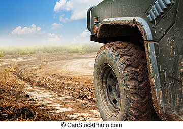 The wheels of car go round on dirt road.