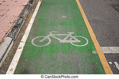 The white bicycle painting on the green bike lane. it is a division of a road marked off with painted lines, for use by cyclists.