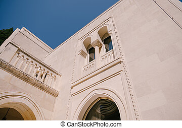 The white facade of the building with arched windows and columns on the balconies, against the blue sky.