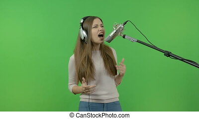 The white girl emotionally sings into the studio microphone. Record a music clip. On a green background