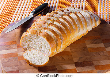 The white loaf cut on pieces on a beautiful wooden chopping...