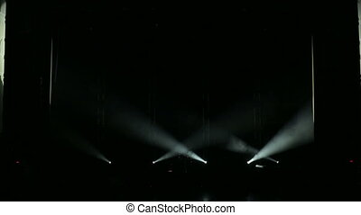 The white rays alternately flash on stage in the dark. Empty concert stage.
