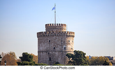 The White Tower in Thessaloniki, Greece. Trees around it. Clear blue sky background.