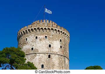 The White Tower in Thessaloniki with waving Greek flag,...