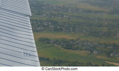 The white wing of a passenger plane against the top view of nature backdrop of green forests and small houses and towns. Travel concept.