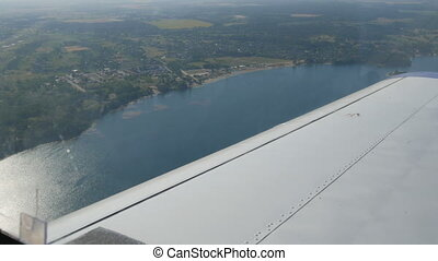The white wing of a passenger plane against the top view of nature backdrop of a beautiful blue lake, flies over a pond, green forests and small houses and towns. Travel concept.