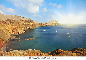 Madeira. Picturesque white yachts in the rocky gulf in the east of the island. Shining rays of the sun reflected in the water