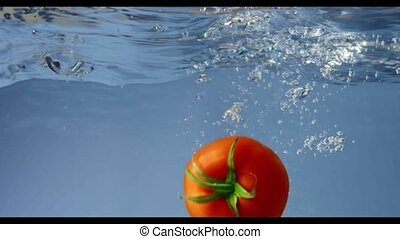The whole tomato falls into clean water. Slow motion. Full...
