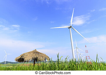 The wind turbine on the rice farm and the hut with the sky and cloud