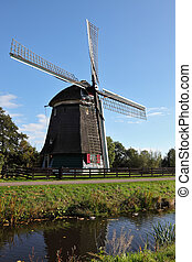 The windmill is reflected in water